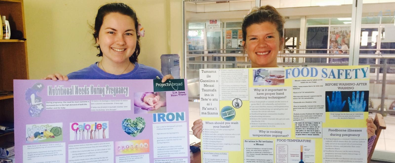 A pair of students doing Nutrition internships abroad with materials they prepared for an education and awareness campaign in local communiities.